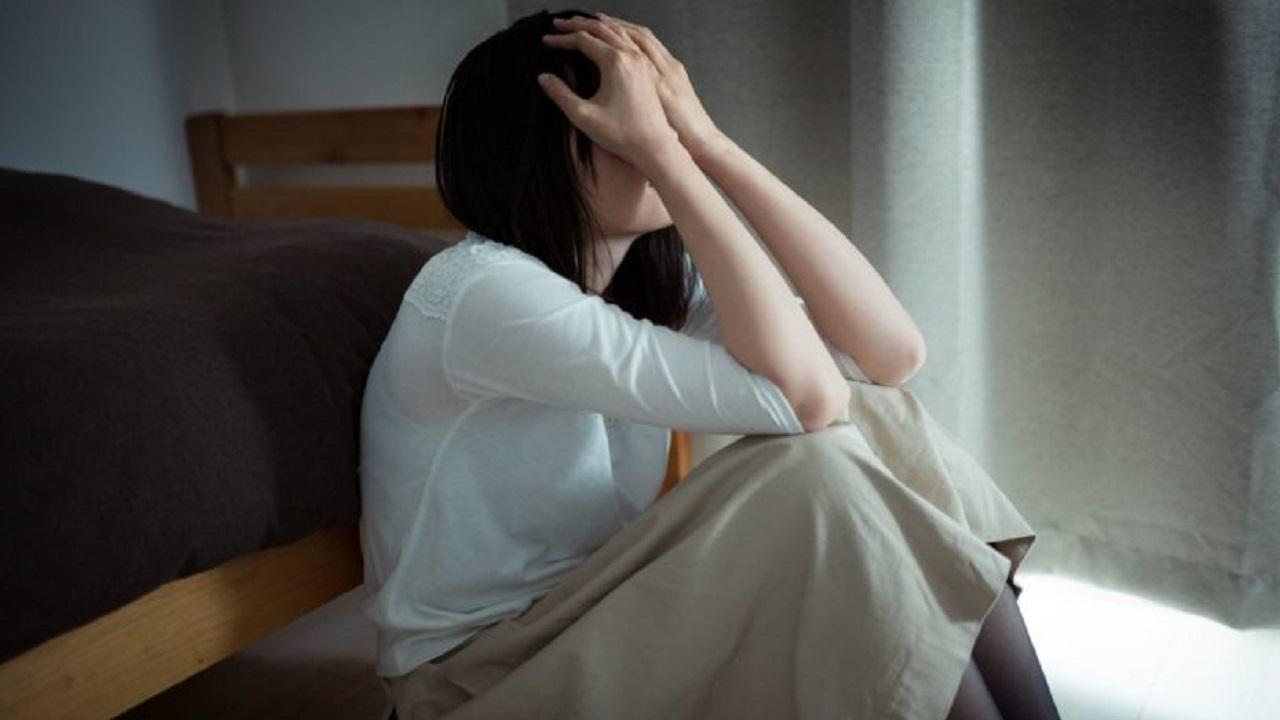 部屋の中でベッドに寄りかかり頭を抱える女性