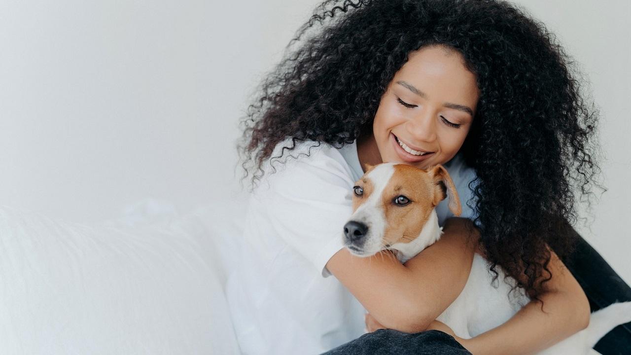 部屋の中で女性が犬を抱きしめている